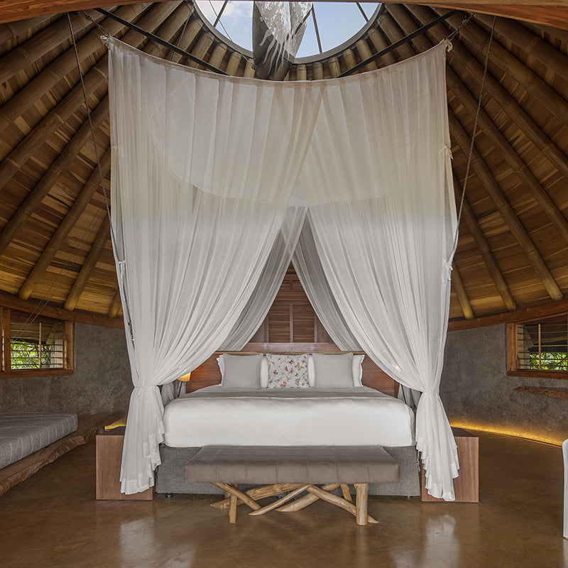 Origins Lodge, Bijagua - hotel room with tall thatch roof ceiling, canopy curtains hanging from the roof over a bed