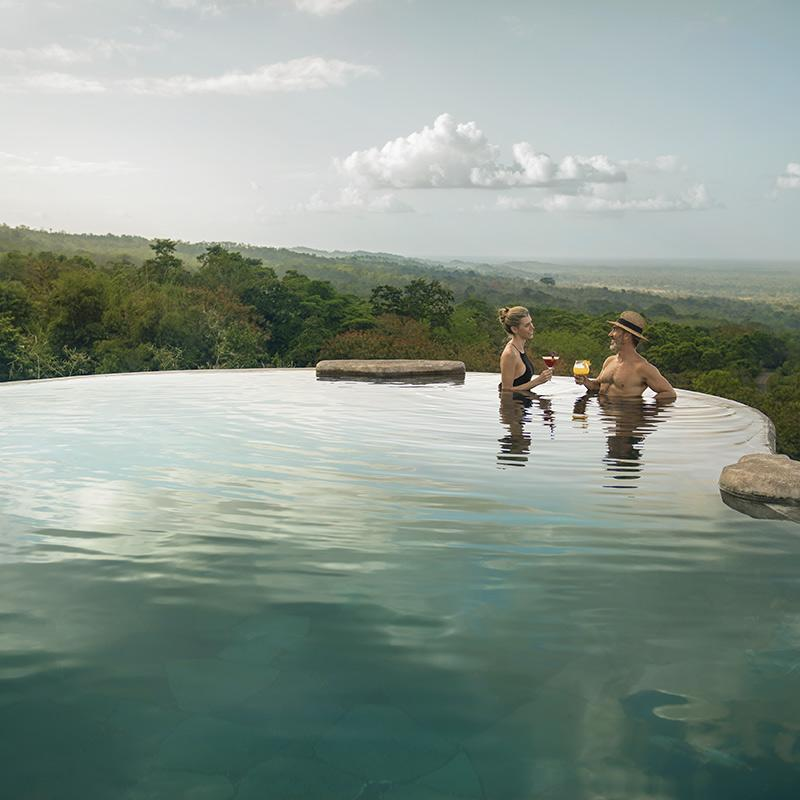 Origins Lodge, Bijagua - man and woman with drinks in an infinity pool overlooking jungle mountains