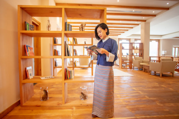 Bhutan Spirit Sanctuary, Bhutan - woman in traditional Bhutanese dress reading a book and standing in front of a large bookshelf