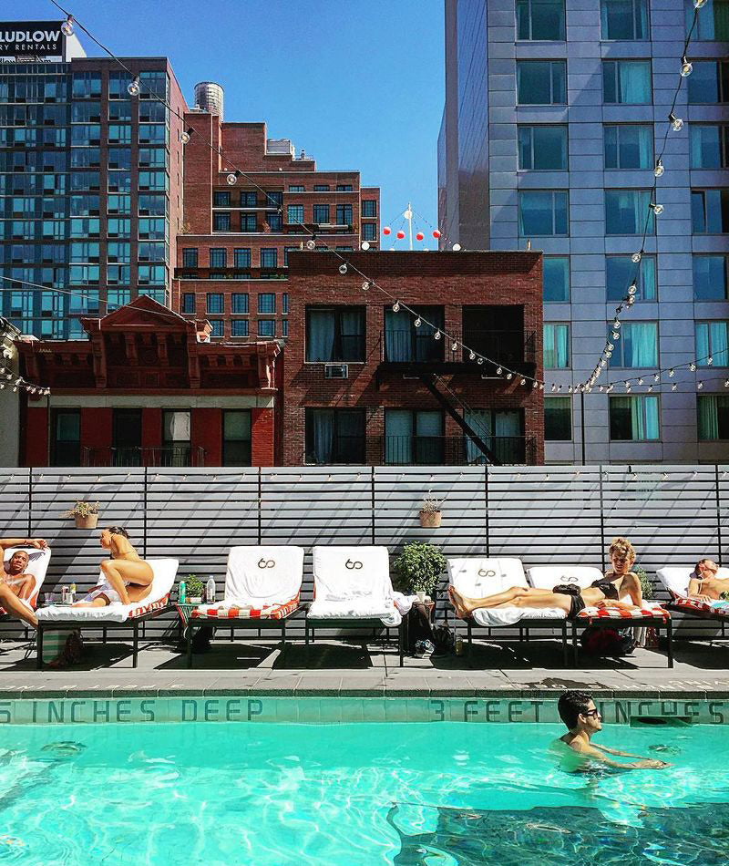 Sixty LES, NYC - rooftop pool with person swimming, people on white lounge chairs, and view of NYC