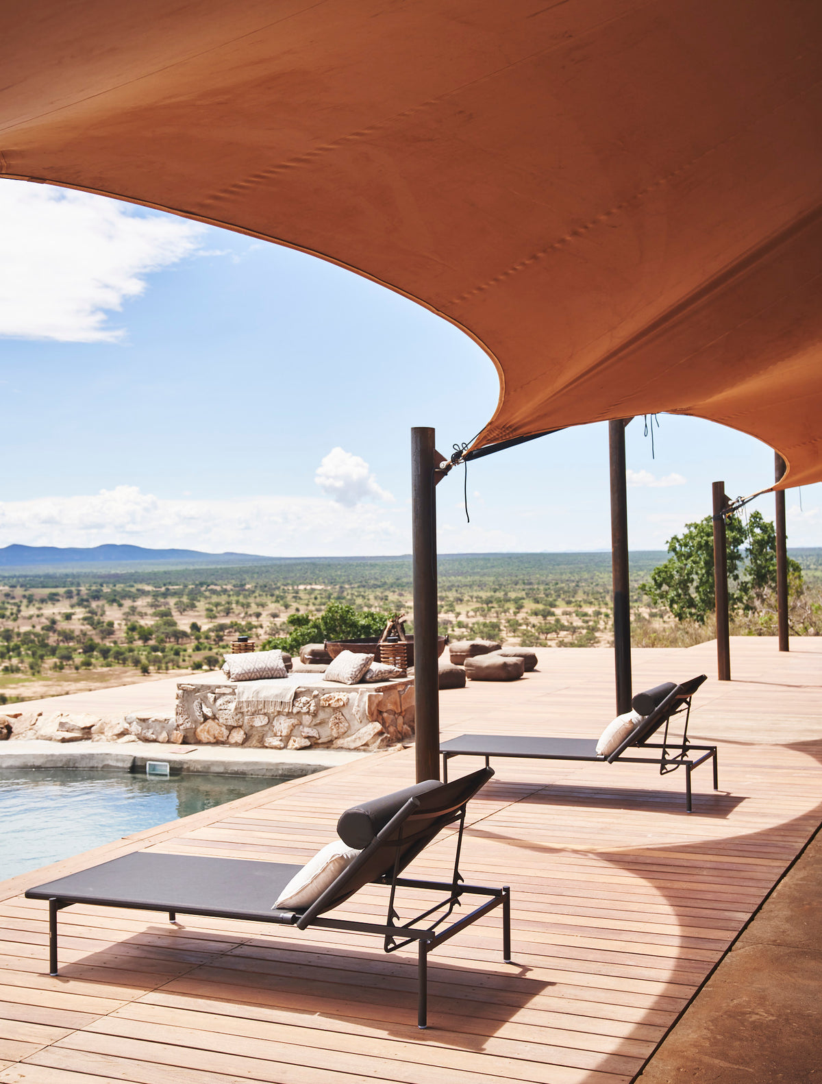 Habitas, Namibia - hotel pool with canvas sunshade, lounge chairs, and a view of bush and mountains