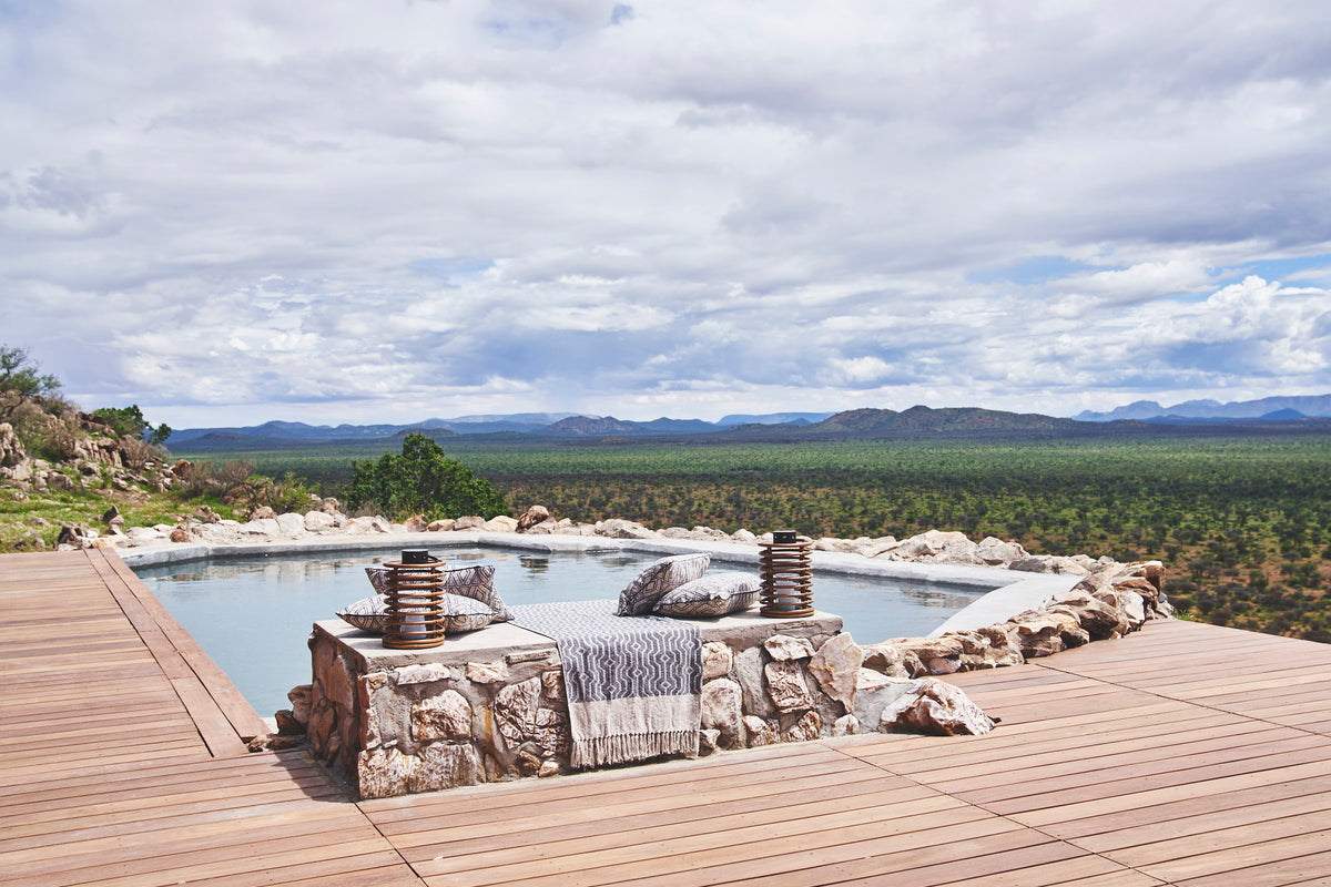 Habitas, Namibia - hotel pool with stone decoration and wooden patio overlooking bush and mountains