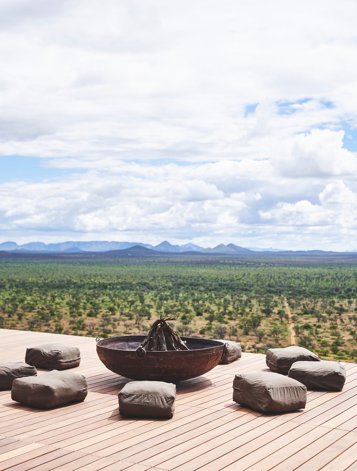Habitas, Namibia - minimalist patio with bean bag cushions around a fire pit overlooking bush and mountains
