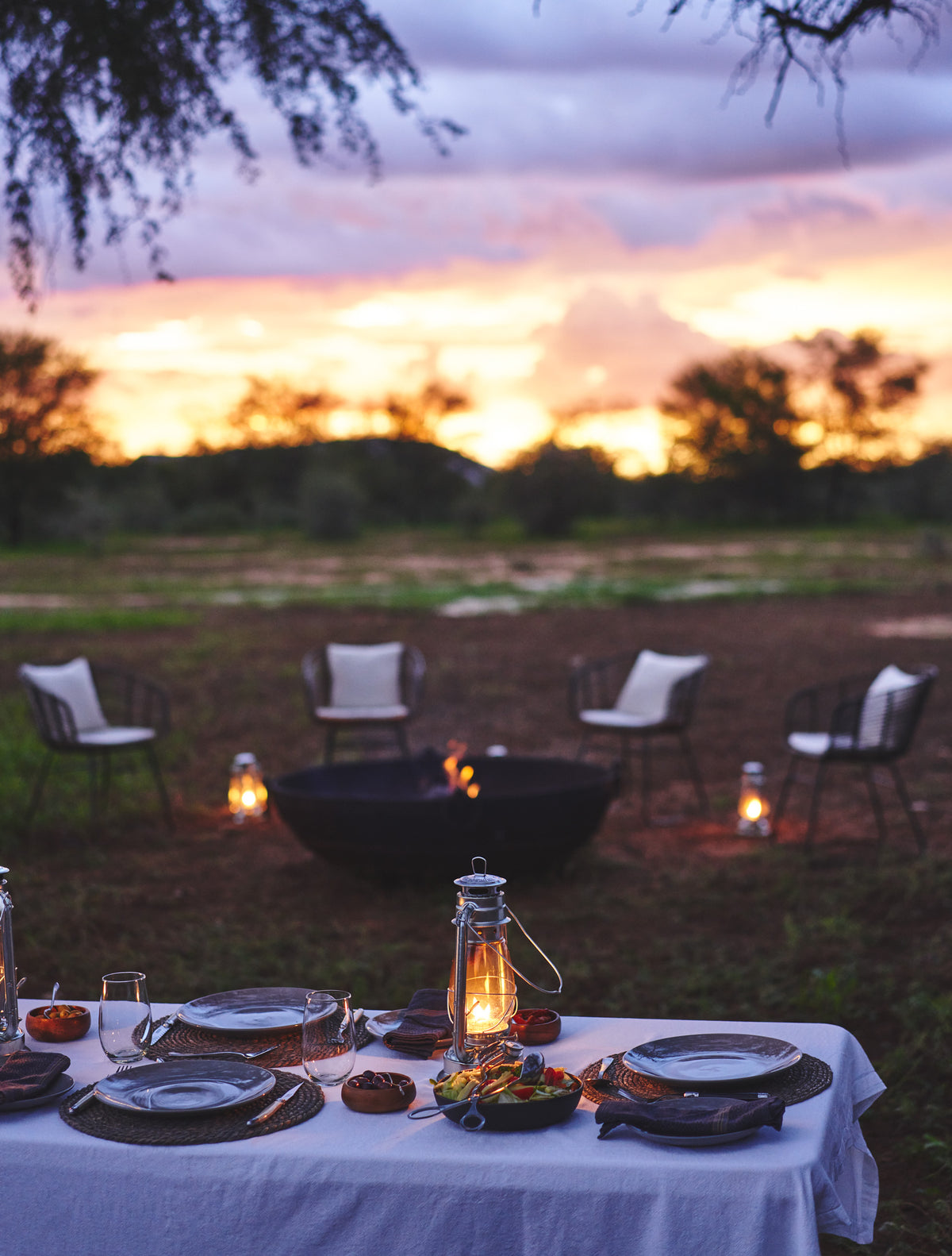 Habitas, Namibia - dinner table set with candle lanterns with a fire pit in the background at sunset