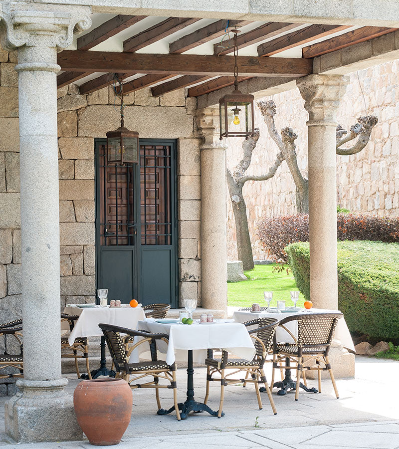 La Casa del Presidente, Ávila - covered patio with stone columns, set tables, and view of manicured walled garden