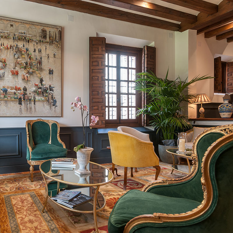 La Casa del Presidente, Ávila - hotel lounge with green and yellow velvet chairs, woven rug, and wooden accents