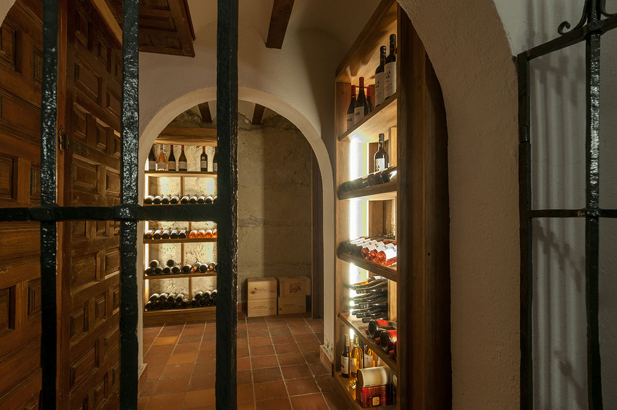 La Casa del Presidente, Ávila - wine cave with iron gate, wooden shelving, and stacked wine bottles