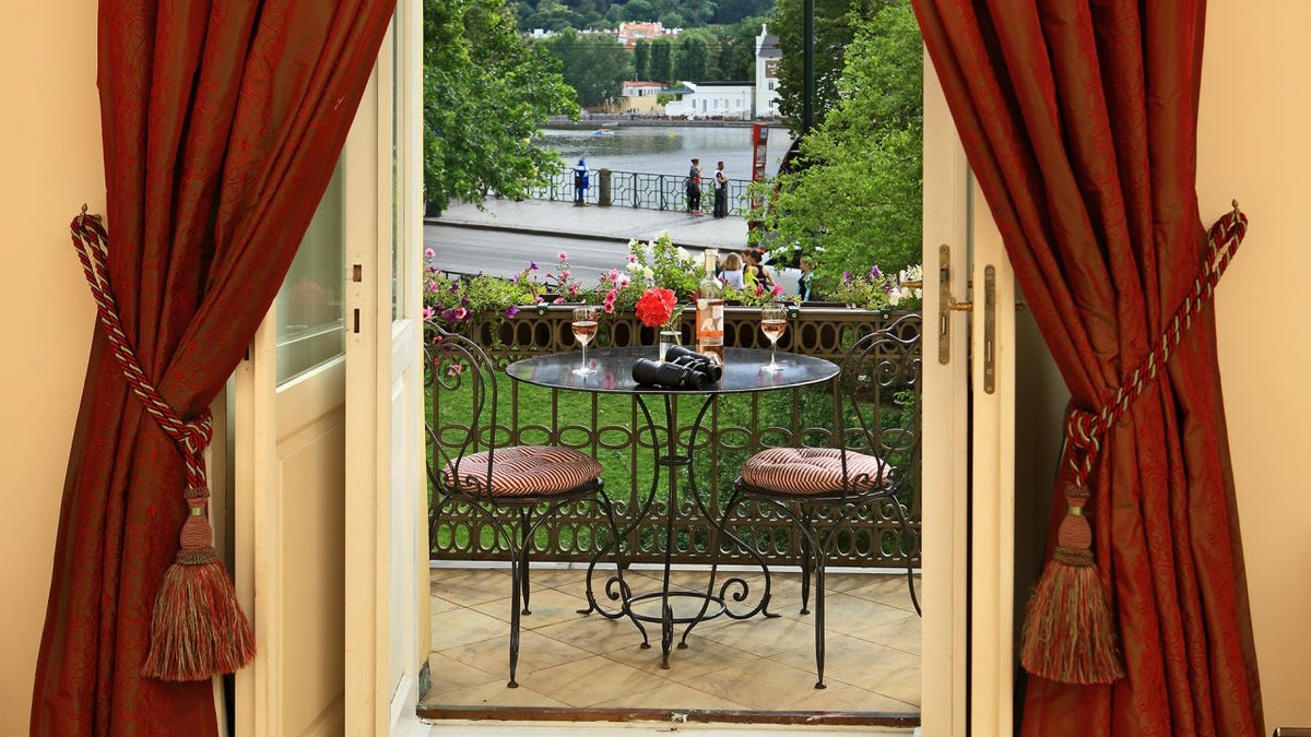 Smetana Hotel, Prague - balcony with table, chairs, wine glasses, and binoculars overlooking street, walkway and Vltava River