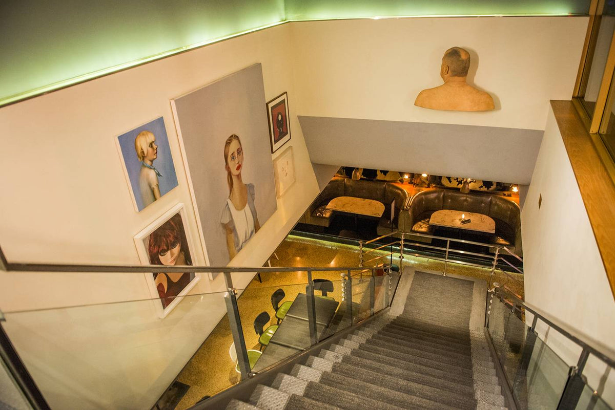 The Drake Hotel, Toronto - looking down on a staircase with painted modern style portraits hanging on the left wall