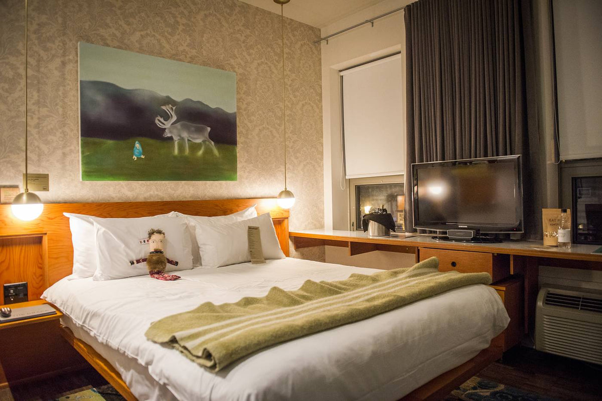 The Drake Hotel, Toronto - hotel room with beige paisley wall paper, retro wooden furniture, and reindeer painting above bed