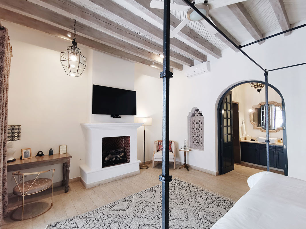 Casa Delphine, San Miguel de Allende - minimalistic hotel room with fireplace, wood beam ceiling, and canopy bed