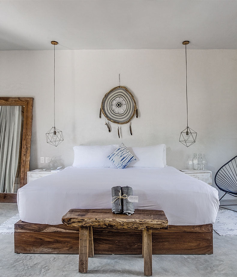 Sanará, Tulum - hotel room with white bed, rustic wooden furniture, hanging geometric lights, and large dreamcatcher behind bed