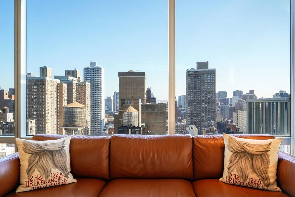 Mondrian Park Avenue, NYC - brown leather couch with large windows behind overlooking NYC skyline