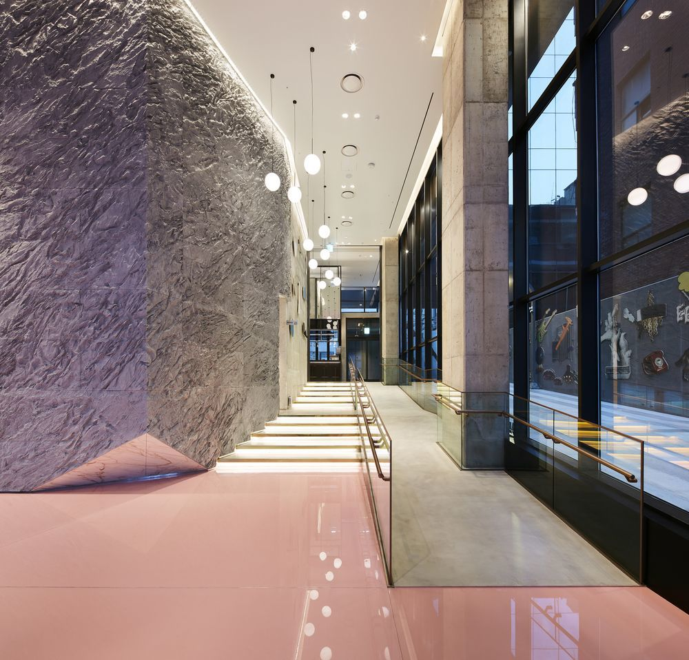 RYSE, Seoul - hotel lobby with sleek pink floor, rock wall on the left, and window wall on the right
