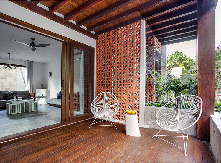 Sanará, Tulum - hotel room with dark wood patio, white wicker chairs, and door leading to room