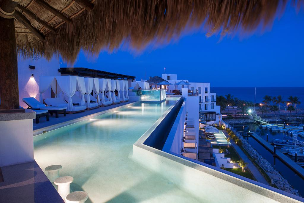 Hotel El Ganzo, Los Cabos - all-white rooftop pool with curtained canopy lounge beds, lounge chairs, and in-pool stools