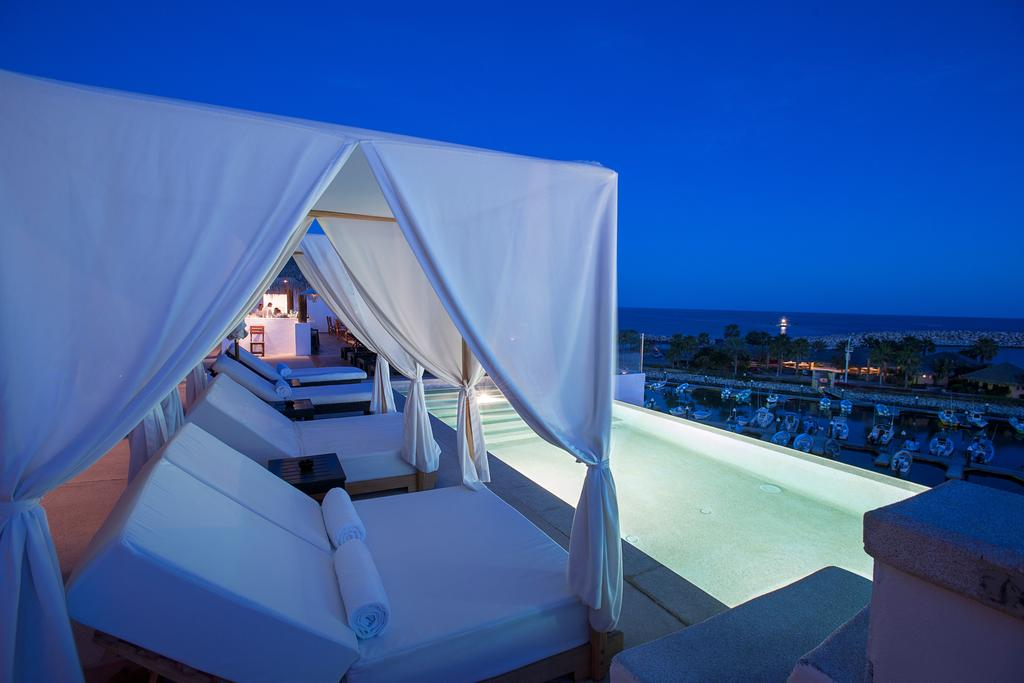 Hotel El Ganzo, Los Cabos - rooftop pool with curtain canopy lounge beds overlooking marina and ocean at night