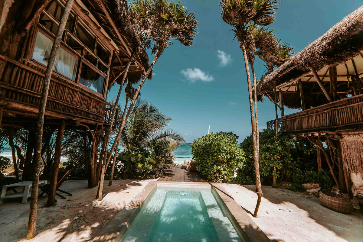 Papaya Playa Project, Tulum - resort pool between two rustic bungalows with turquoise ocean view