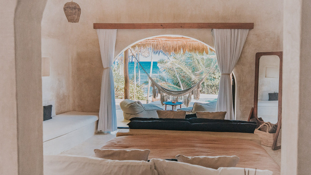 Papaya Playa Project, Tulum - hotel room with bed, doorway overlooking patio with a hammock and bean bag chairs, and an ocean view
