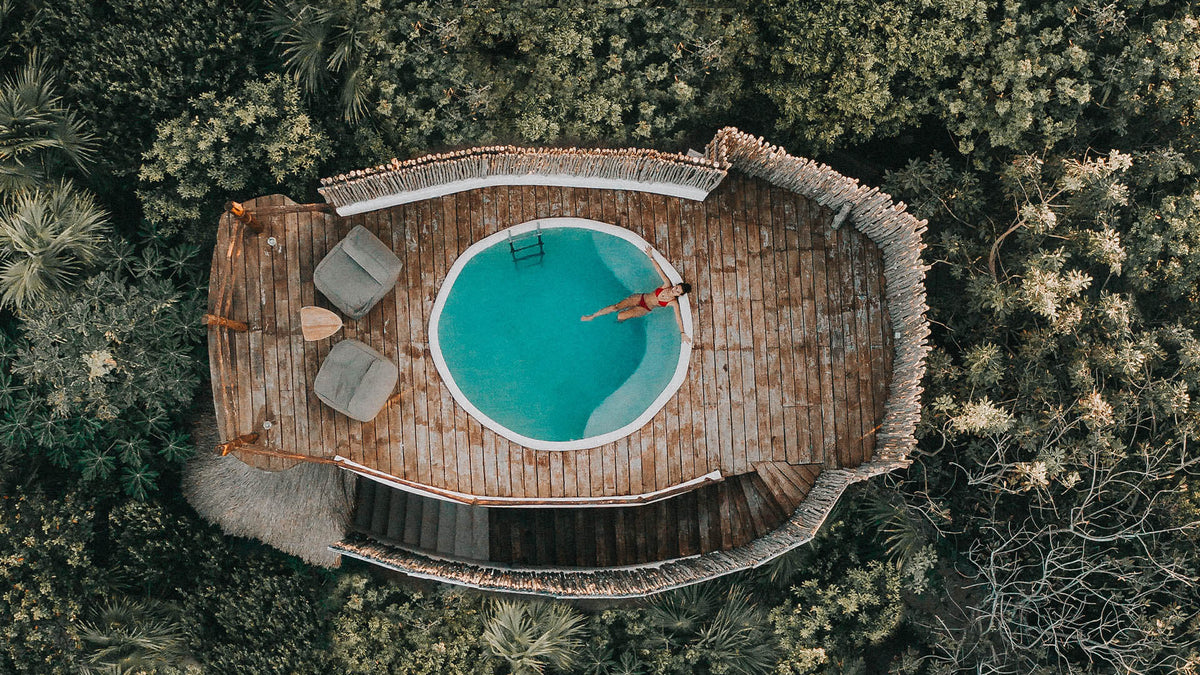 Papaya Playa Project, Tulum - bird's eye view of private bungalow rooftop pool with bean bag lounges and a woman in the pool