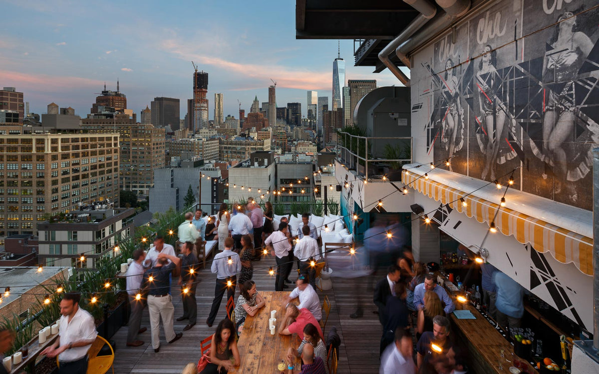 Hotel Hugo, NYC - Azul rooftop bar with couches, coffee tables, chairs, barstools, bar, and sunset city view