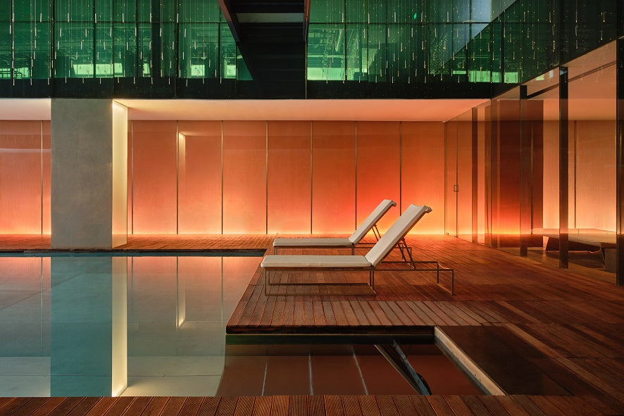 The Opposite House, Beijing - indoor hotel pool with wood deck, sleek columns, and white lounge chairs