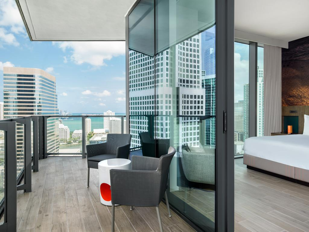 EAST, Miami - private hotel balcony with chairs, a coffee table, and view of the city and ocean