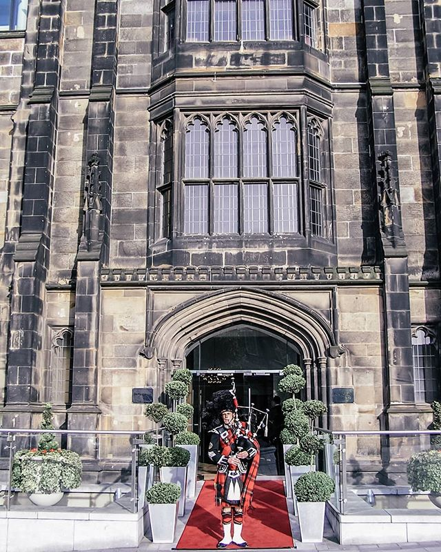 The Glasshouse, Edinburgh - hotel exterior, gothic church facade with man in kilt outside playing bagpipes