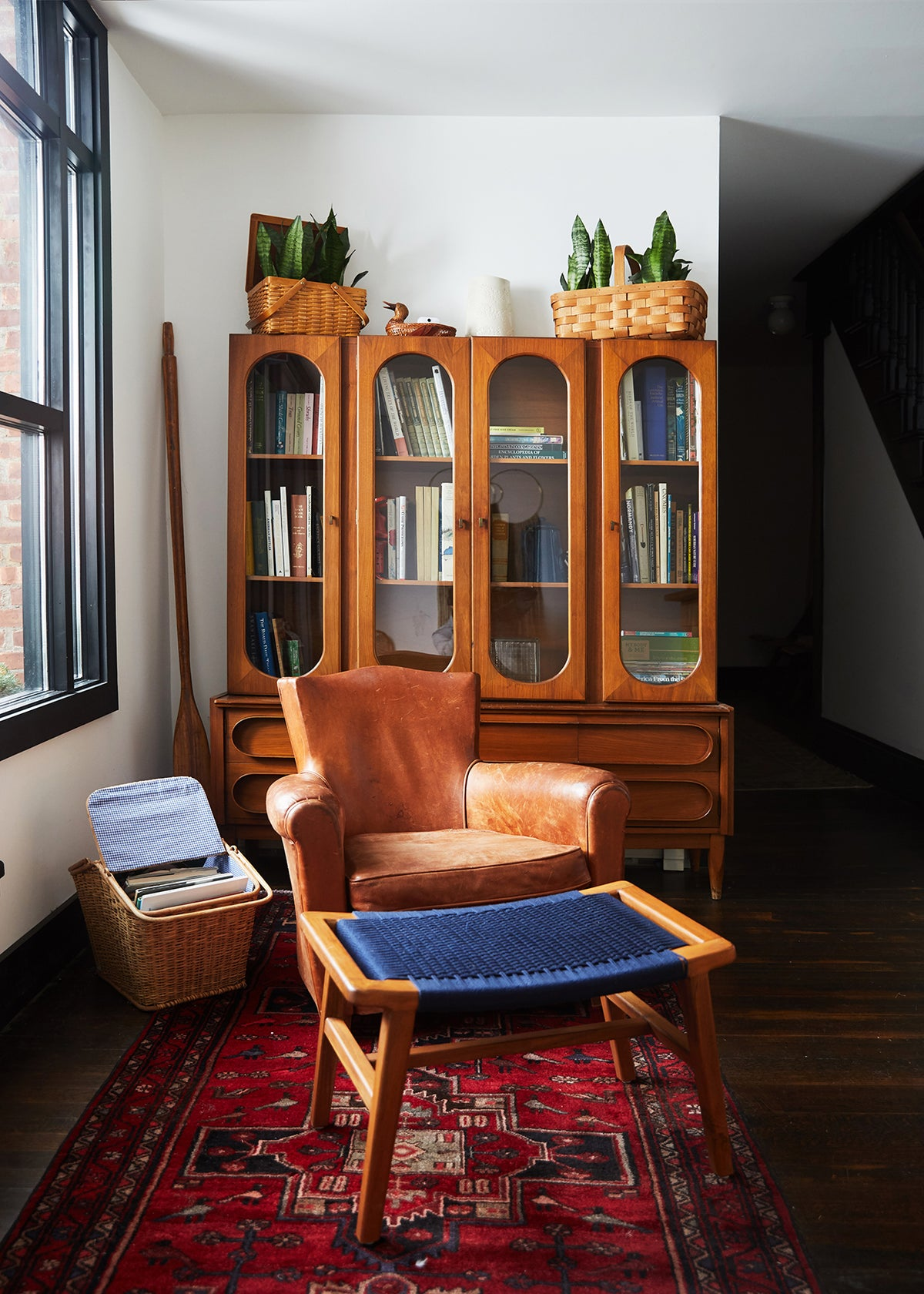 Eastwind Hotel & Bar, NY - hotel nook with a leather armchair, fabric ottoman, and vintage bookcase