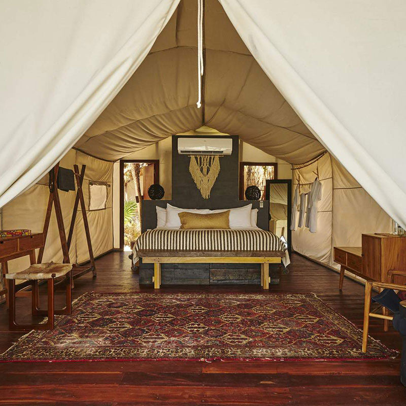 Habitas, Tulum - glamping tent with bed, desk, chairs, and entryway