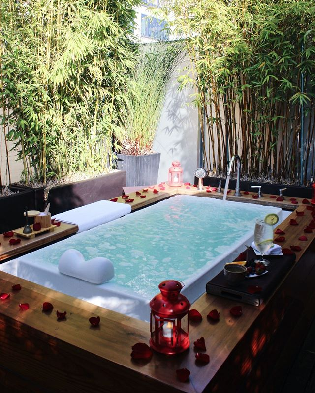 Hotel Vitale, San Francisco - private pool with flower petals and lamps around the edge and shaded by bamboo