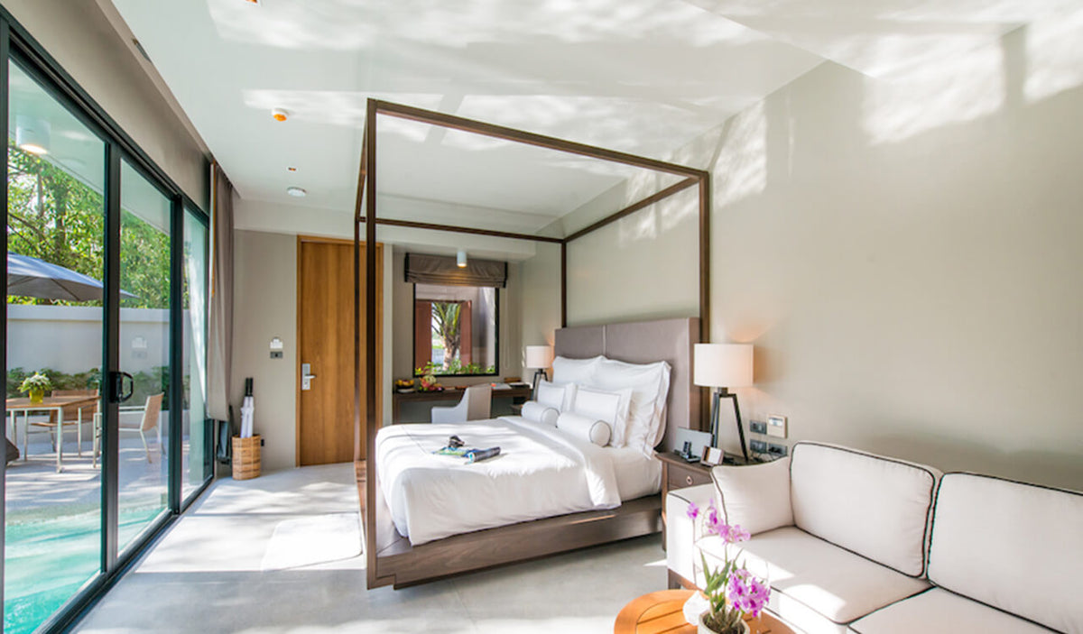 Aleenta Phuket Resort & Spa, Phuket - hotel room with canopy bed, couch, desk, and sliding doors leading to private patio