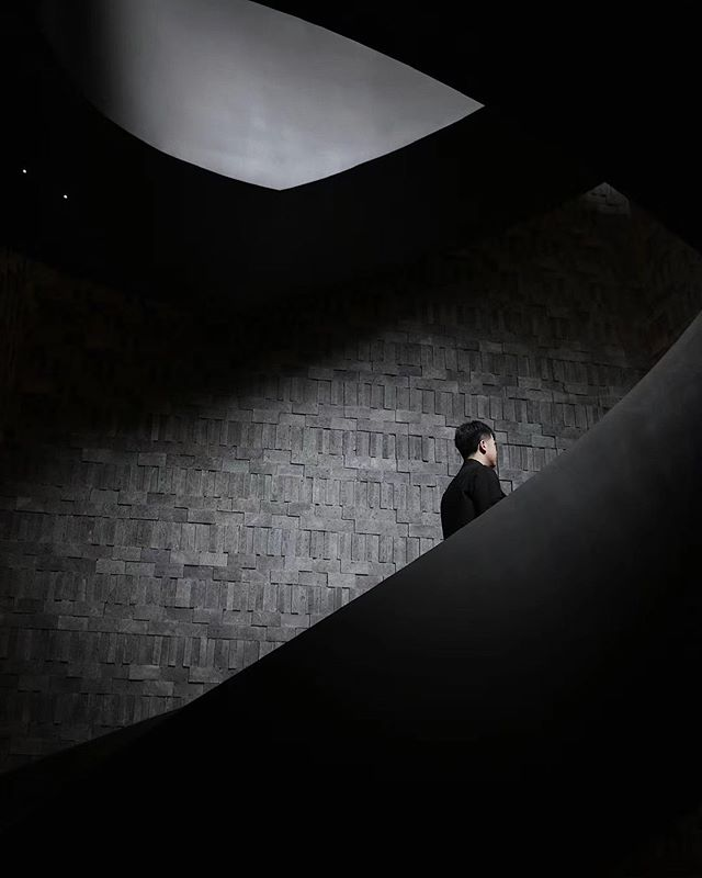 The Middle House, Shanghai- man climbing a dark staircase against textured wall