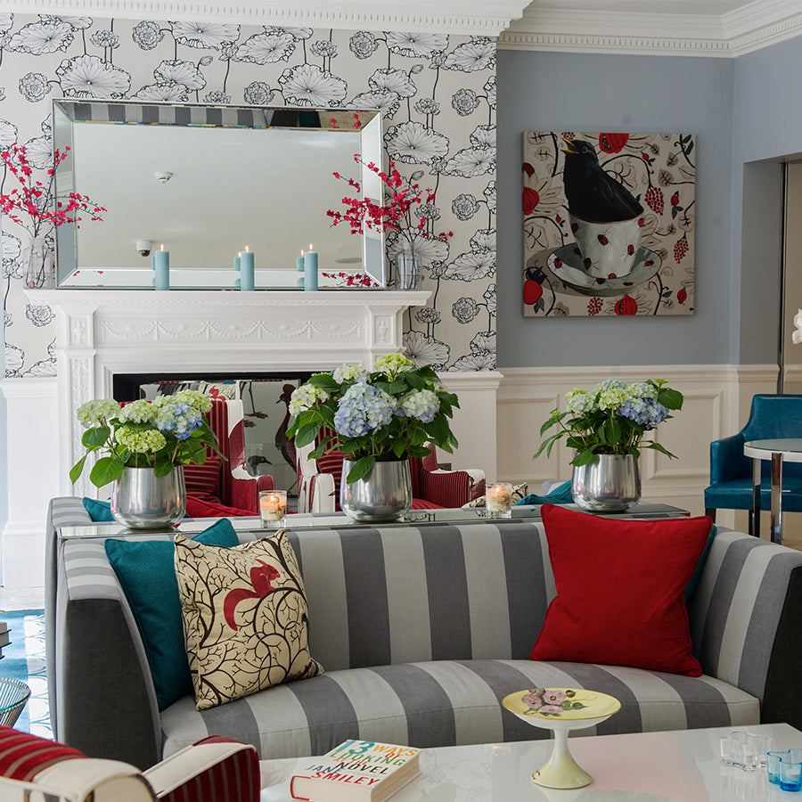 The Ampersand Hotel, London - Drawing Room tea room with striped grey couch, red and blue decorations, and hydrangeas in a vase