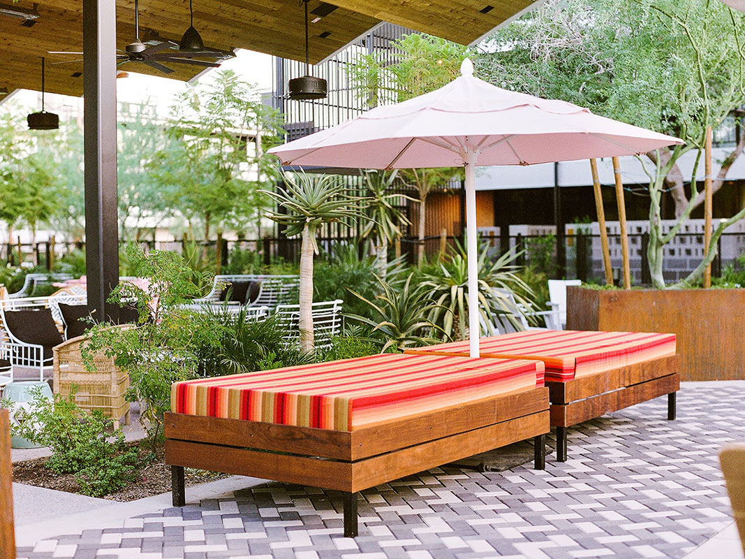 ARRIVE Phoenix, Phoenix, AZ - hotel patio with striped lounge bed and pink sun umbrellas