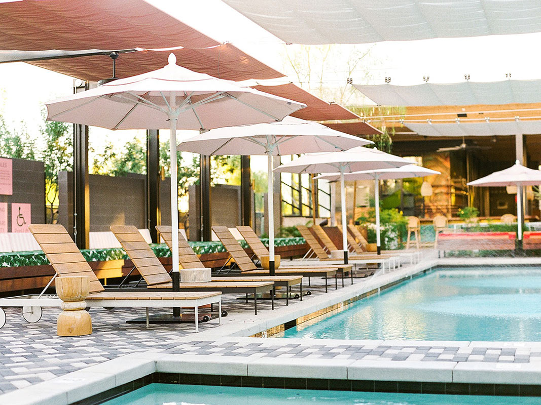 ARRIVE Phoenix, Phoenix, AZ - hotel pool with wooden lounge chairs and umbrellas