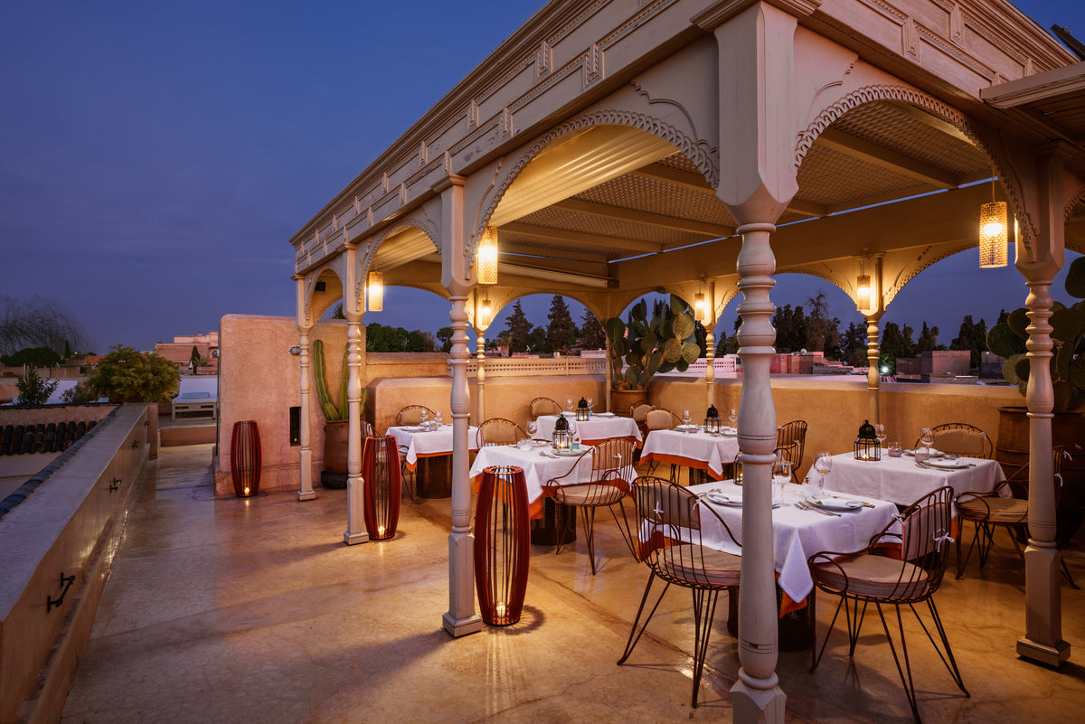 72 Riad, Marrakech, Morocco - hotel rooftop with set tables under intricately carved pavilion at night