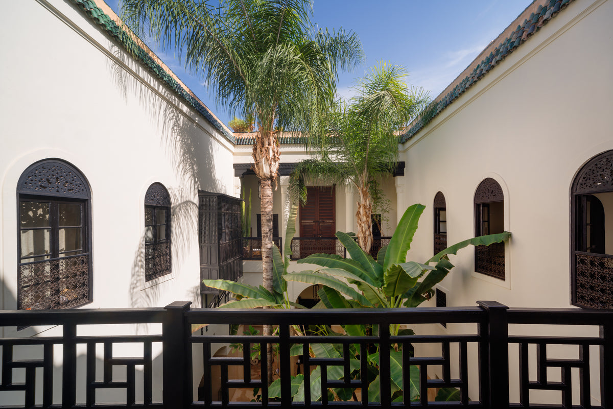 72 Riad, Marrakech, Morocco - hotel courtyard on second level with intricate windows overlooking large palm trees