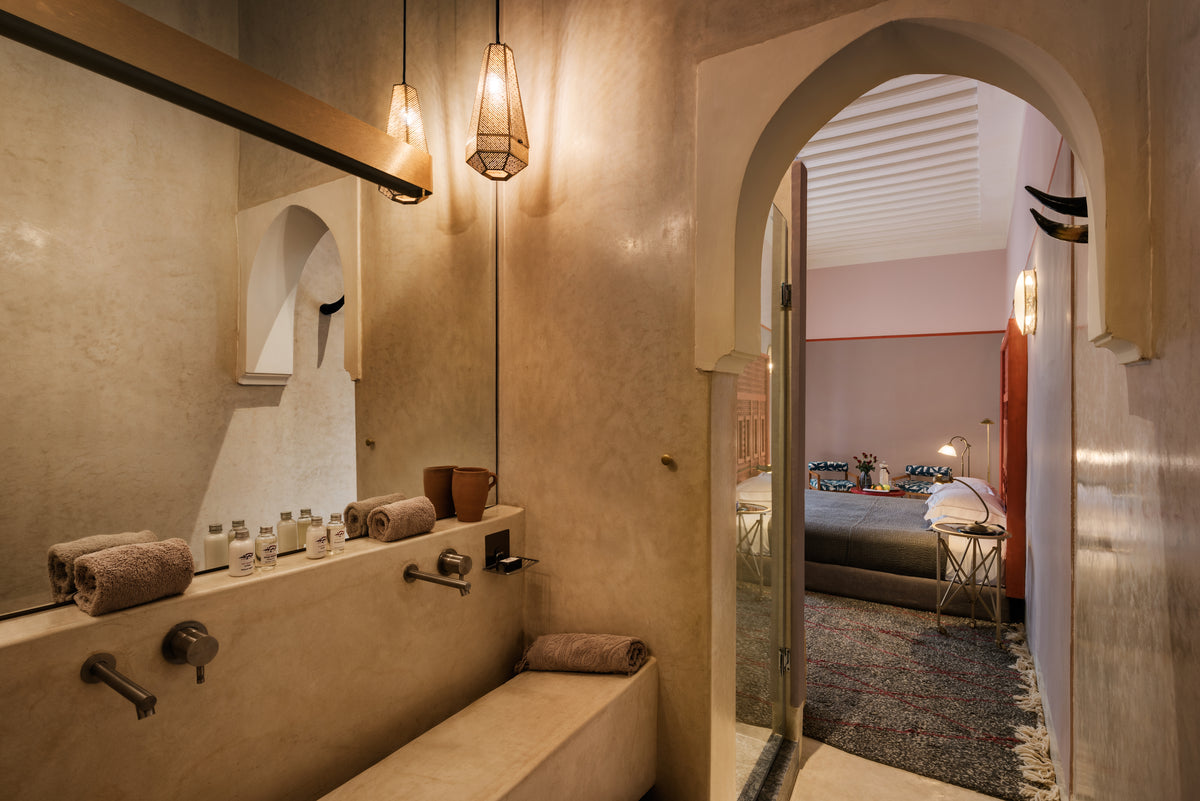 72 Riad, Marrakech, Morocco - hotel bathroom with stone walls and matching double sink with arched doorway leading to bedroom