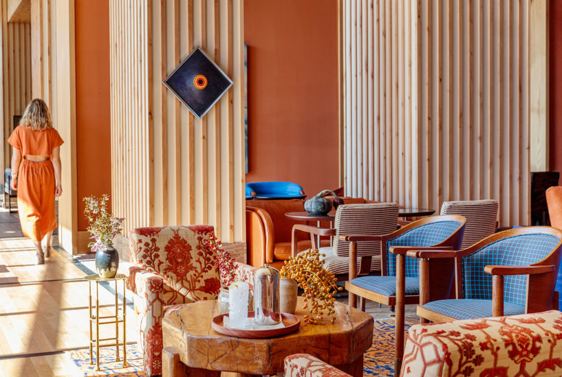 Austin Proper Hotel, Austin - colorful hotel lobby with orange walls and blue armchairs