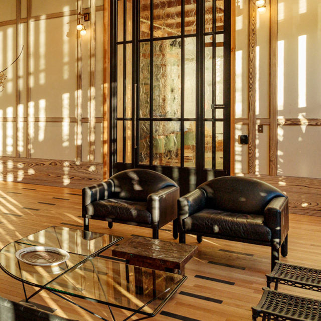 Austin Proper Hotel, Austin - hotel lobby with armchairs, wooden wall beams, and sunset light streaming through windows