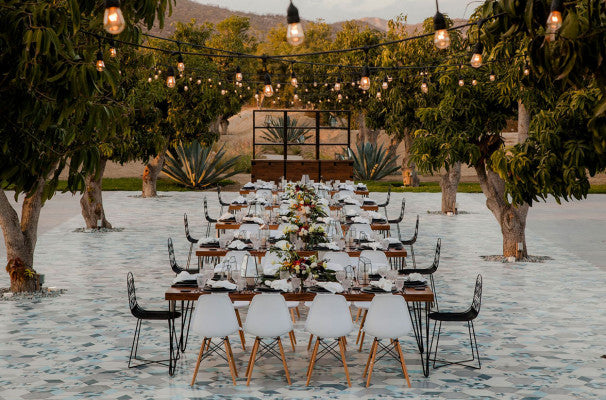 Acre, Los Cabos - outdoor banquet with set tables, chairs, string lights, and trees