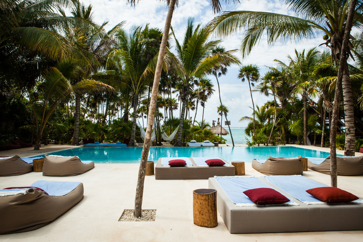 Jashita Hotel, Tulum - hotel pool with lounge chairs, lounge beds, palm trees, and ocean view