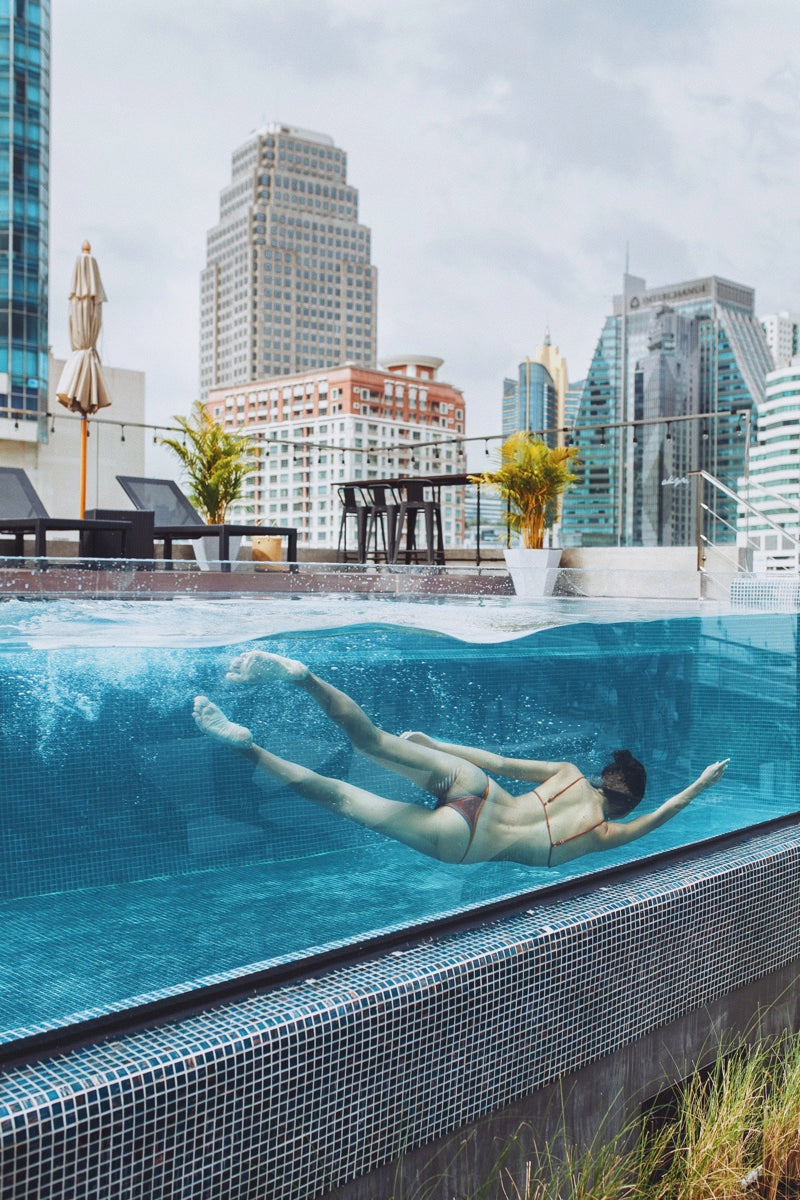 Akyra TAS Sukhumvit Bangkok - woman swimming in a rooftop glass pool with lounge chairs and daytime city view
