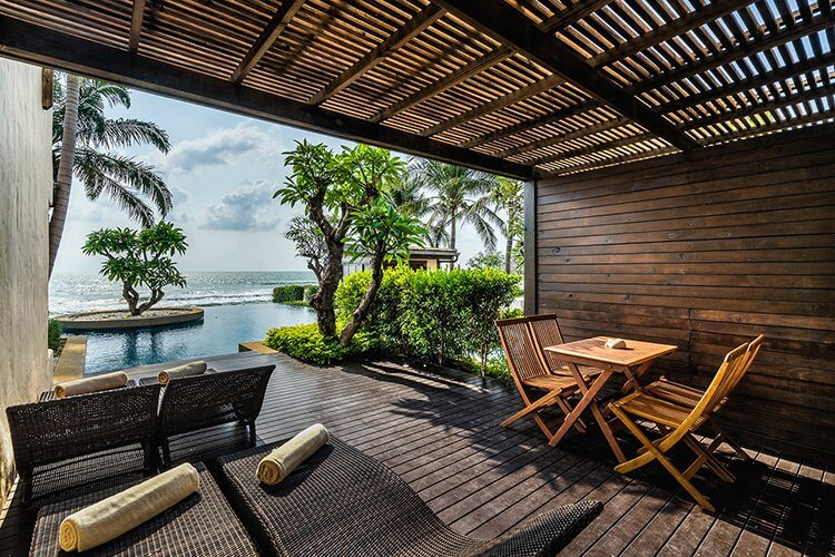 Aleenta Hua Hin Resort & Spa, Pranburi - covered patio with lounge chairs, table, and a view of an infinity pool leading to a beach