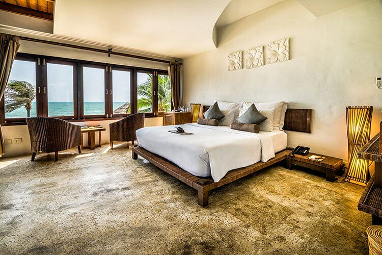 Aleenta Hua Hin Resort & Spa, Pranburi - nature-inspired hotel room with a king size bed, wicker chairs, and beach view windows
