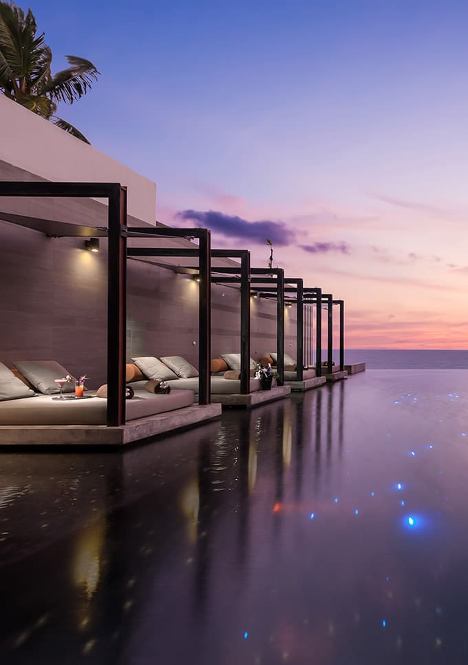 Aleenta Phuket Resort & Spa, Phuket - tropical outdoor infinity pool with lounge beds at sunset
