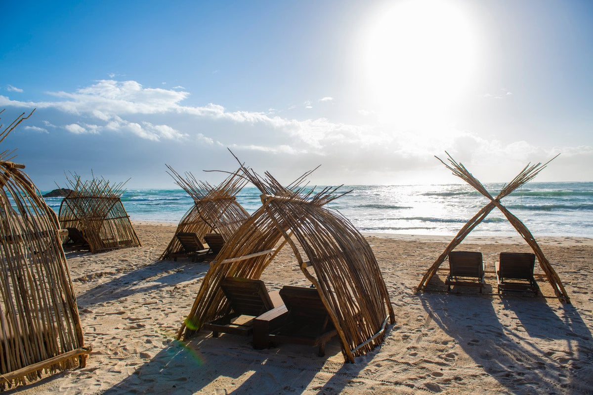Amansala, Tulum - rustic wooden sun tents with lounge chairs on a beach
