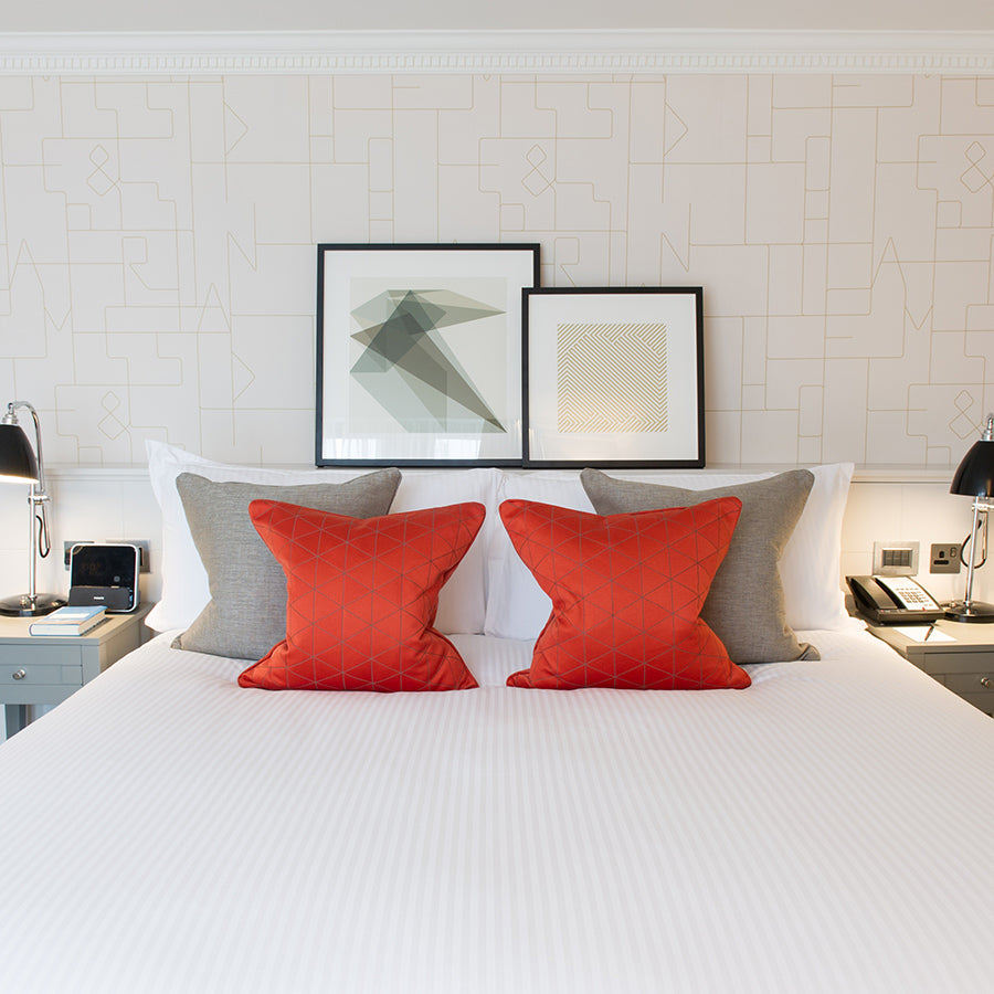 The Ampersand Hotel, London - minimalist hotel room with beige wall, abstract framed art, and red throw pillows on white bed