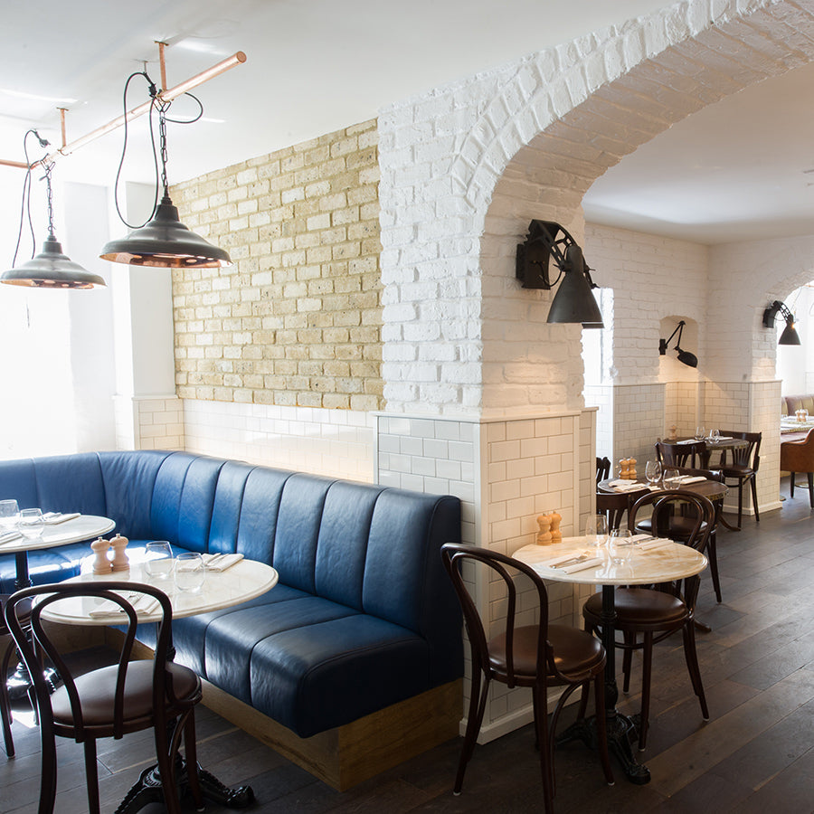 The Ampersand Hotel, London - Apero bar and lounge with blue booth couches, wooden chairs, and white brick arches and walls